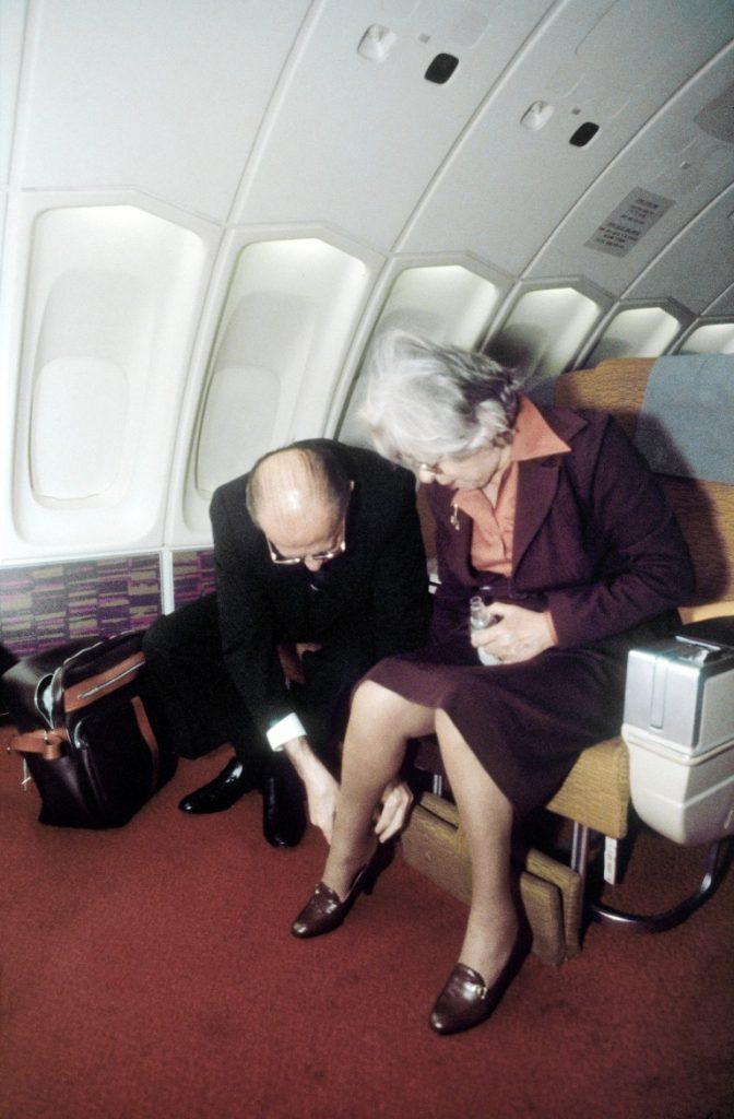 """ראש הממשלה מנחם בגין מסייע פולה ודוד בן גוריון בצריף שדה בוקר לאשתו עליזה לנעול נעליים בטיסה לארה""""ב / 1978"""