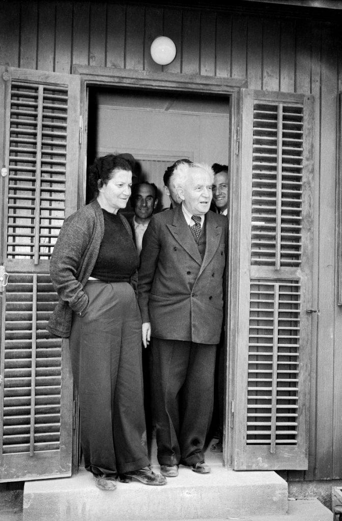 דוד בן גוריון ראש הממשלה שהתפטר עבר לגור ב קיבוץ שדה בוקר ב נגב דוד בן גוריון ו אשתו פולה עומדים ב פתח הצריף שלהם ב קיבוץ שדה בוקר DAVID BEN-GURION Prime.Min. with Paula Ben-Gurion After resignation,arriv.in Sde Boker. W/Paula.Hut.Dininghall Sde-Boker 19531214 PAULA BEN-GURION with BEN-GURION In Sde Boker Diningroom, after arrivall there , following BG's resignation Sde-Boker